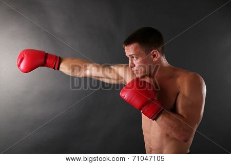 Handsome young muscular sportsman with boxing gloves on dark background