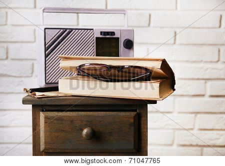 Retro radio, book and glasses on table in room