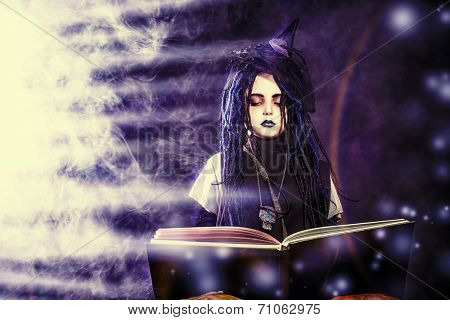 Little girl in a costume of witch casts a spell over magic book over dark background.