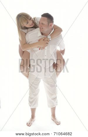 Playful laughing romantic couple having fun as the woman enjoys a piggy back ride on the mans back, upper body facing the camera isolated on white