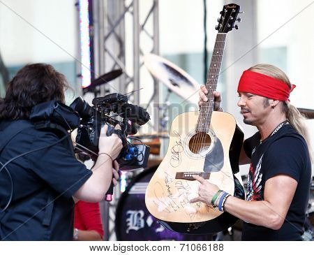 NEW YORK-JUL 18: Recording artist Bret Michaels autographs a guitar to be donated at the Hard Rock Cafe at Fox and Friends' All-American Summer Concert Series on July 18, 2014 in New York City.