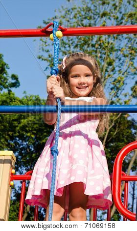 Smiling Little Girl Playing On Playground Equipment