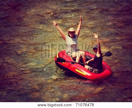 two girls floating down a river in an inflatable raft toned with a retro vintage instagram filter effect