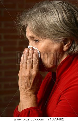 Sick elder woman in red