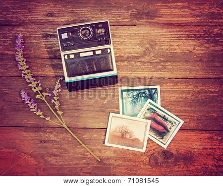 Vintage photo camera on a wooden table with some snapshots and a flower toned with a retro vintage instagram filter effect