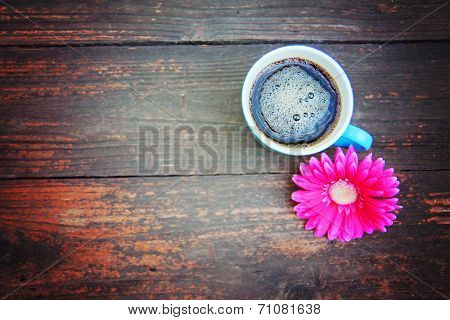 a cup of coffee and a flower on a wooden texture background