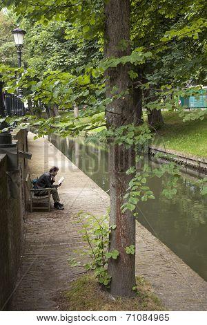 Man Reading On Bench At Nieuwegracht In Utrecht