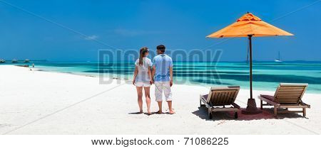Back view of a couple on a tropical beach vacation panorama perfect for banners
