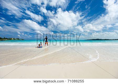 Beautiful tropical beach at Exuma Bahamas with father and son having fun