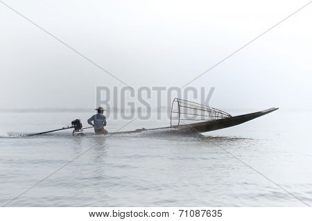 Myanmar, Shan state, Inle lake Intha fisherman on boat at early morning with fog and mist background