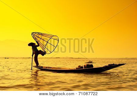 Myanmar, Shan state, Inle lake Intha fisherman on boat at amazing sunset