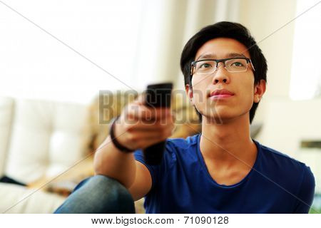 Serious man sitting on couch watching tv at home in the living room