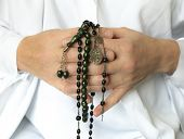 picture of prayer beads  - A person in white folds hands in prayer clasping beads representing different faiths - JPG