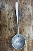 stock photo of ladle  - Old tin ladle on a wooden background from above - JPG