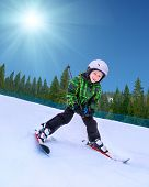 stock photo of snowy hill  - Little skier going down from snowy hill - JPG