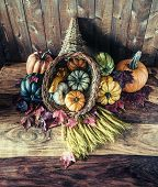 stock photo of cornucopia  - A cornucopia with squash gourds pumpkins wheat and leaves on an old antique table.