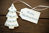 foto of weihnachten  - A Blue German Frohe Weihnachten which means Merry Christmas on a white Label with a Christmas Tree Cookie - JPG