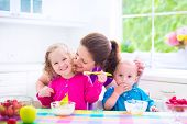 stock photo of brother sister  - Happy young family mother with two children adorable toddler girl and funny messy baby boy having healthy breakfast eating fruit and dairy sitting in a white sunny kitchen with window - JPG