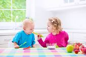 image of child feeding  - Two little children adorable toddler girl and funny baby boy eating yoghurt with berry and fruit together sister feeding brother having healthy breakfast in a white sunny kitchen with window - JPG