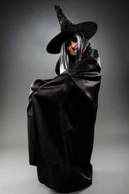 stock photo of sorcerer  - Full length of a sorcerer with hat and cape over gray background  - JPG