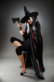 foto of sorcerer  - Full length of a sorcerer with hat and cape over gray background holding an axe - JPG