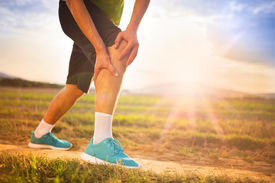 stock photo of short legs  - Runner leg and muscle pain during running training outdoors in summer nature - JPG