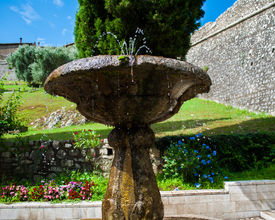 stock photo of gushing  - stone fountain gushing fresh water into a beautiful flower garden