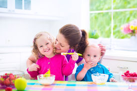picture of breakfast  - Happy young family mother with two children adorable toddler girl and funny messy baby boy having healthy breakfast eating fruit and dairy sitting in a white sunny kitchen with window - JPG