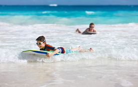 image of boogie board  - Mother and son n vacation having fun swimming on boogie board - JPG