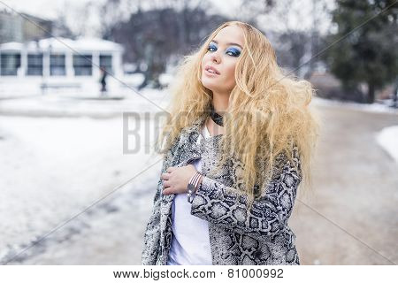 Blonde lady is posing in the city park
