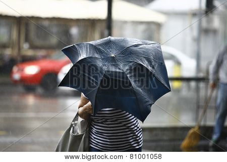 Woman Walking With Umbrellas In The Rainy City