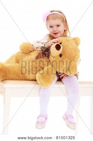 Adorable little girl hugging a teddy bear.