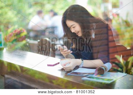 Young Asian Woman Using The Phone In Coffee Shop