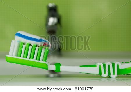 Green toothbrush on a green background