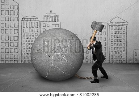 Businessman Holding Hammer Hitting Cracked Concrete Ball With Buildings Doodles