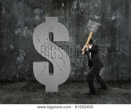 Businessman Holding Hammer Hitting Cracked Dollar Sign With Mottled Wall