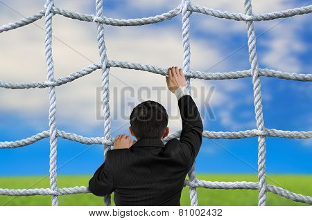 Businessman Climbing Crisscross Rope Net On Sky Cloud Grass Background