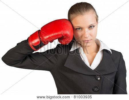 Businesswoman holding boxing glove at her temple