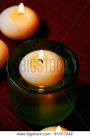 Glass Candlesticks And Candles On Wooden Table. Selective Focus On The Candle In The Glass