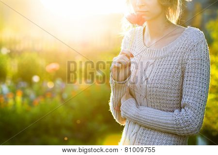 Young woman holding a poppy flower in evening sunlight.