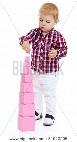 little boy builds Red Pyramid, Montessori Kindergarten