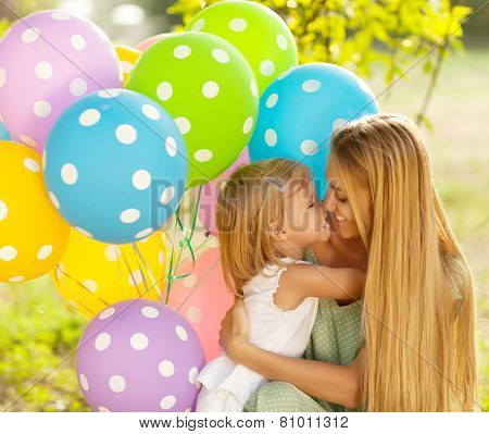 Happy Woman And Her Little Daughters With Ballons Outdoors