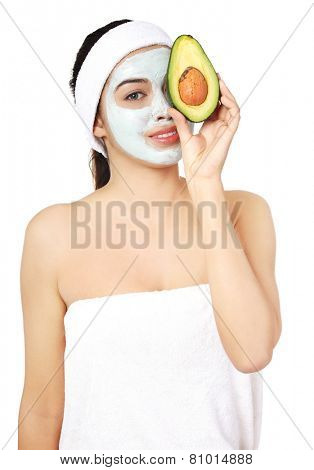 Beautiful spa woman in facial mask and avocado.