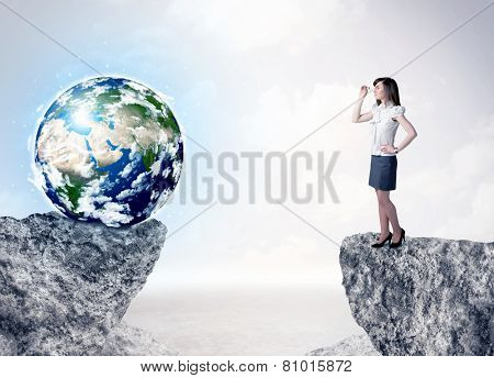 Businesswoman standing on the edge of mountain with a globe on the other side,   '