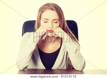 Beautiful casual bored or sleeping student woman by a desk.