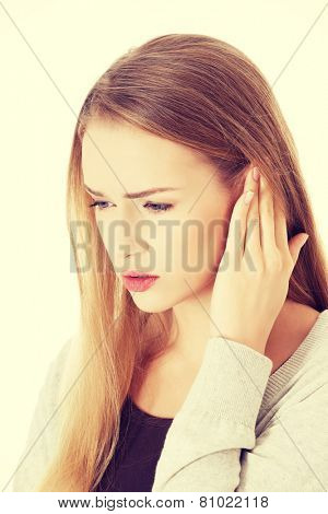 Beautiful casual woman is touching her ear. Health concept.