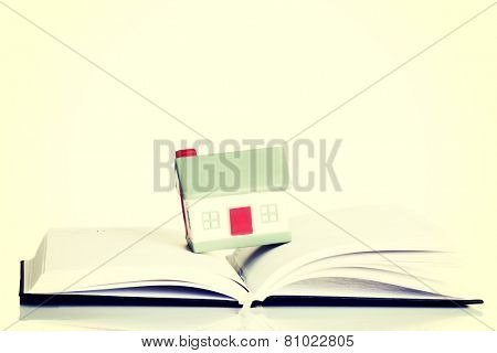 Small house standing on an open book.