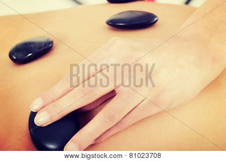 Female's back having stone massage. Spa concept.