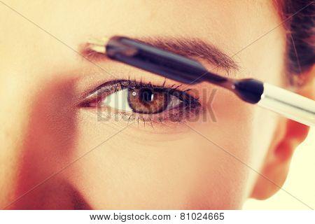 Beautiful woman brushing her eyebrow. Close up.