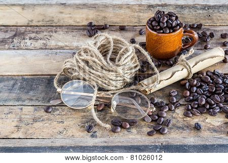 Old Paper Roll, Glasses, Rope Reel And Coffee Beans On Wooden